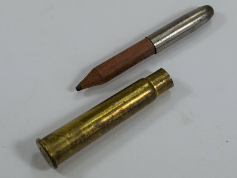 "An original WW1 bullet pencil, the case is the standard .303 service rifle case and is dated 1914, we can see no signs of an ""M"" monogram to the neck. The head is of white metal and the original to the case. The wooden pencil looks to be a replacement."